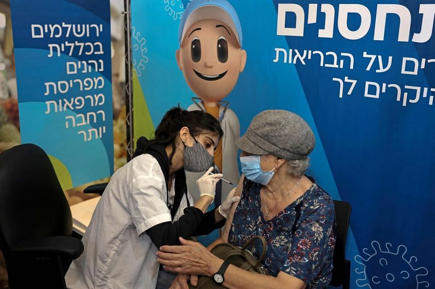 An Israeli health worker administers a third dose of the Pfizer-BioNtech Covid-19 vaccine at the new vaccination centre for Clalit Health Services on Aug 8, 2021.