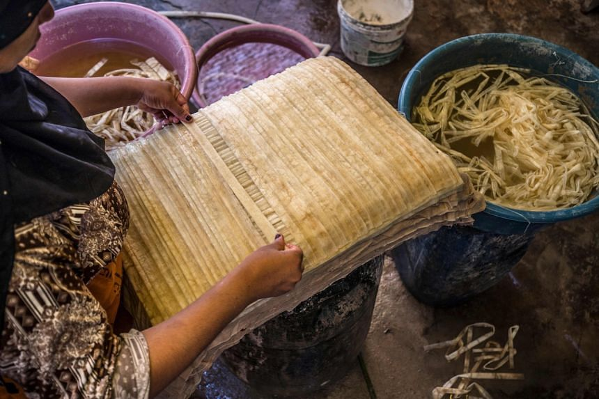 A woman lays out soaked thin strips of papyrus to form a sheet.