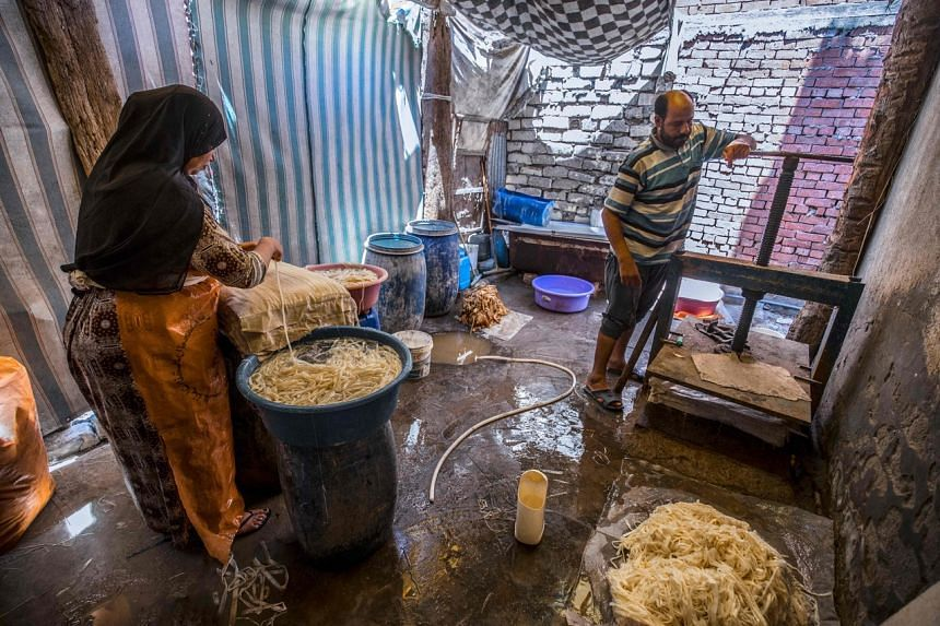 Mr Abdel Mobdi Moussalam and an assistant prepare soaked papyrus strips before compression and drying.