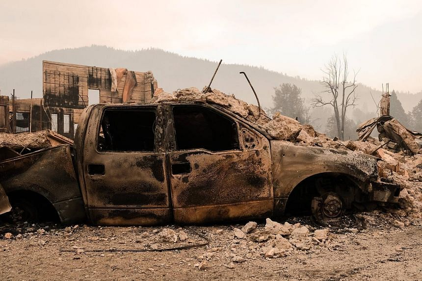 A charred vehicle destroyed by the Dixie Fire in front of the remains of a structure situated near Highway 89 in Greenville, California, on Sunday.
