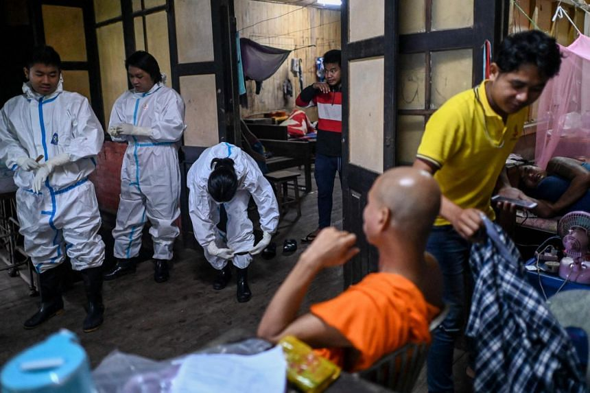 Medical volunteers putting on personal protective equipment before leaving their temporary base in Taungoo district, in Myanmar's Bago region, on Aug 7, 2021.