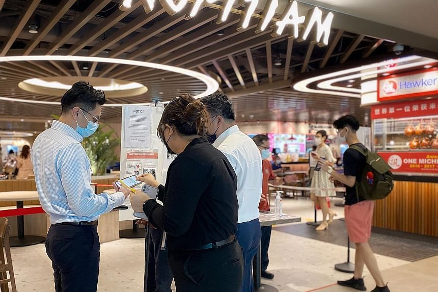Patrons having their vaccination status checked on their TraceTogether mobile app by foodcourt staff at Plaza Singapura on Tuesday. Only fully vaccinated individuals will receive a yellow sticker and are allowed to dine in, while those non-fully vacc