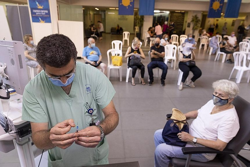 A health worker preparing a booster dose of the Pfizer-BioNTech Covid-19 vaccine at a medical centre in Tel Aviv on Aug 2, 2021.