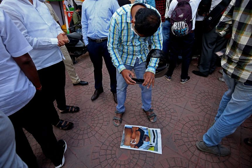 A photograph of a Congolese man who died in police custody is seen on a footpath outside a police station in Bangalore, India, on Aug 2, 2021.