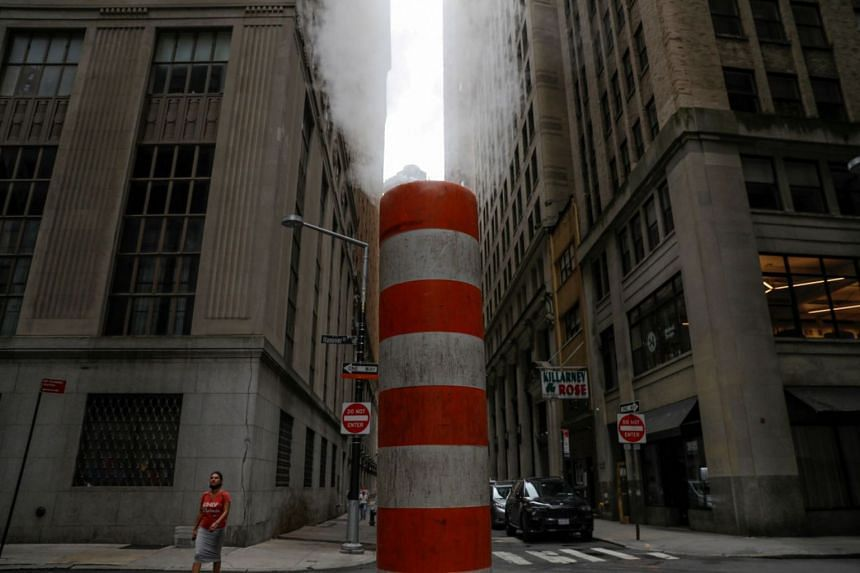 A person walks by a steam pipe in the Financial District after The United Nations released the Intergovernmental Panel on Climate Change's (IPCC) latest report, in Manhattan, New York City.