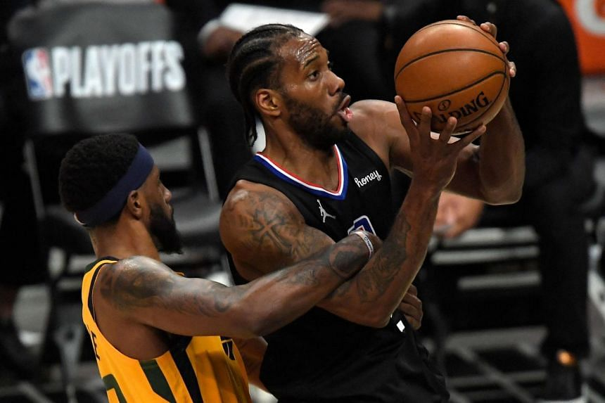 Royce O'Neale (left) ties up Kawhi Leonard after fouling him during the Western Conference second-round playoff series at Staples Center on June 14, 2021.