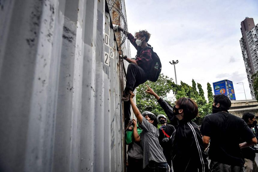 A protester climbs a wall of shipping containers during a demonstration calling for the resignation of Thai PM Prayut Chan-o-cha, in Bangkok, on Aug 13, 2021.