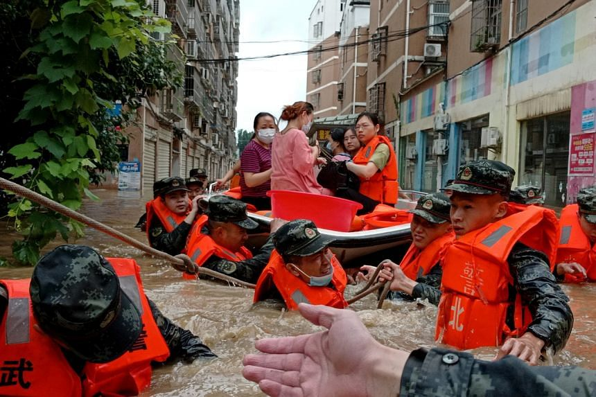 Paramilitary police officers evacuate residents stranded in floodwaters following heavy rainfall in Hedian, Suizhou, in Hubei province on Aug 12, 2021.