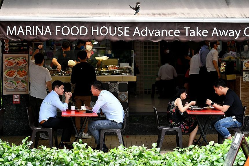 People dining in at Marina Food House in Phillip Street on Thursday. Following the latest set of rules which kicked in on Tuesday, only hawker centres and coffee shops are able to accept groups of two diners regardless of vaccination status.
