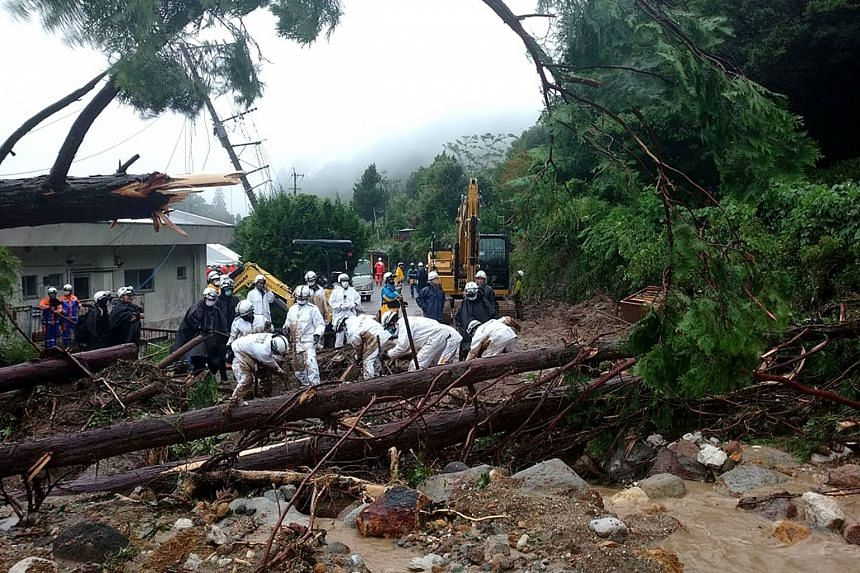 Rescue workers searching for missing persons at the site of a mudslide caused by heavy rain in Unzen, on Aug 14, 2021.