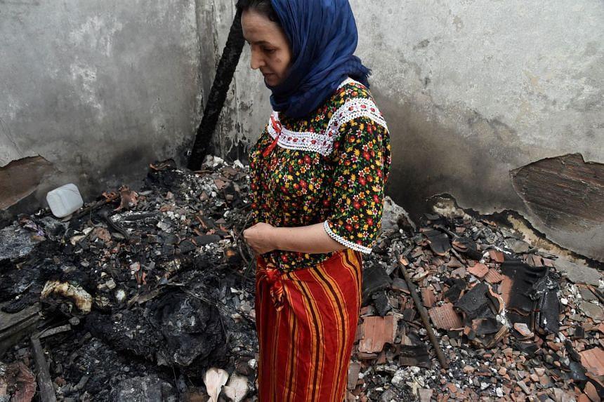 An Algerian woman dressed in a traditional outfit stands amid the charred debris of her home on Aug 13, 2021.