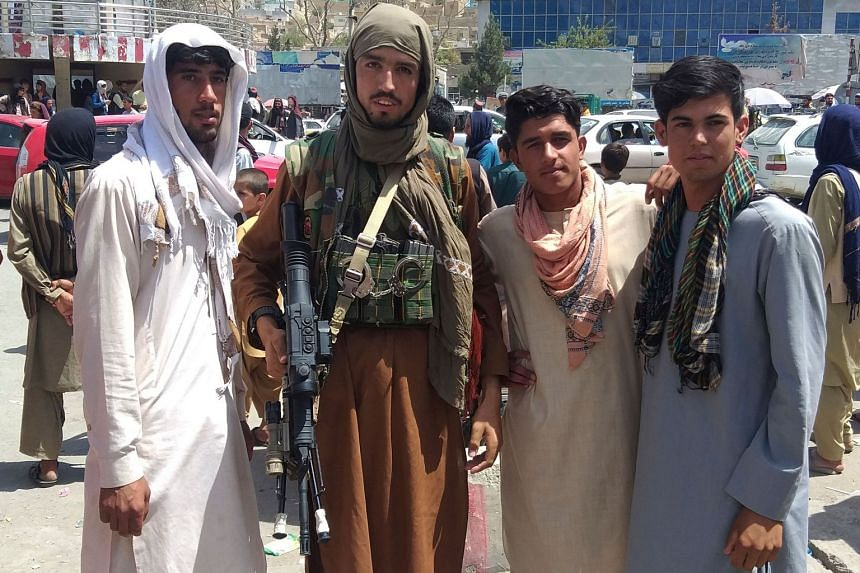 A Taleban fighter with local residents of Pul-e-Khumri after the Afghan city was seized by the group on Wednesday.
