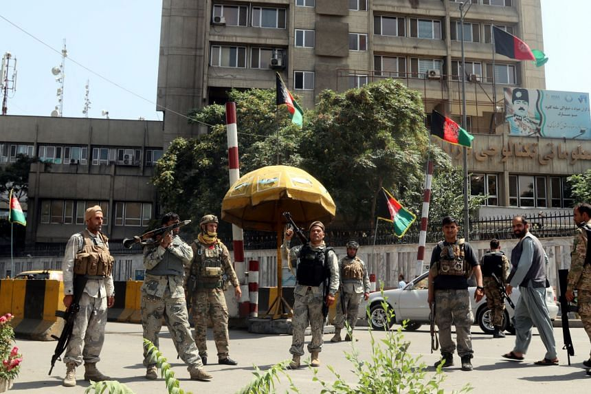 Afghan security officials stand guard at a checkpoint in Kabul on Aug 15, 2021.