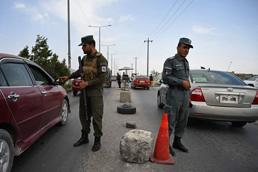 Policemen standing guard at a checkpoint in Kabul on Aug 14, 2021.