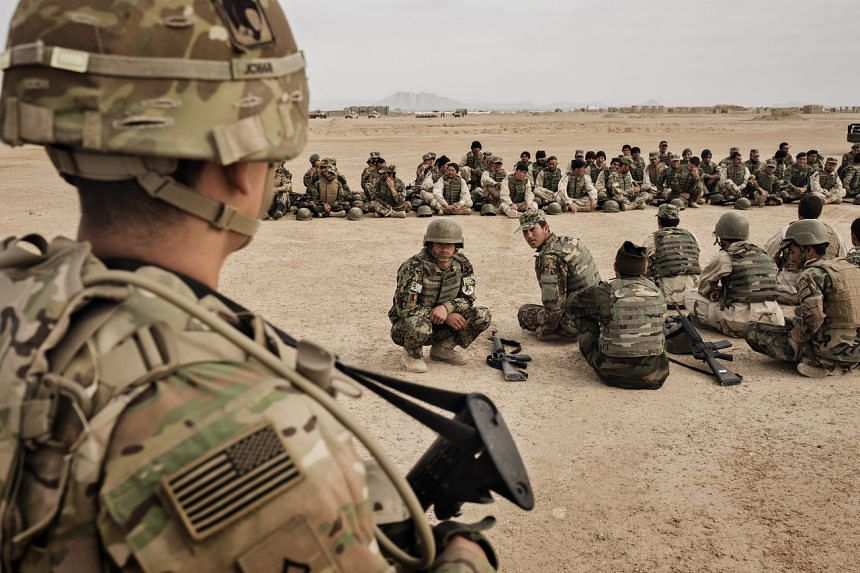 A photo from March 22, 2016, shows American soldiers overseeing training of their Afghan counterparts in Helmand province, Afghanistan.