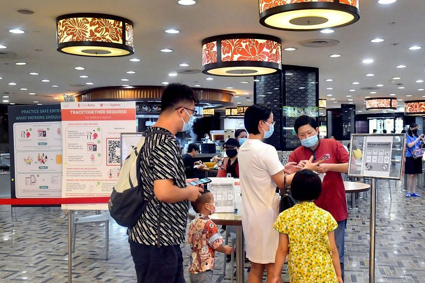 Diners checking in and having their vaccination status checked at Hougang Mall yesterday. A green tick in the TraceTogether app denotes that the person has completed the full vaccination regimen.
