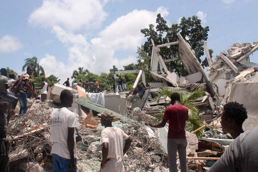 People search through the rubble of what used to be the Manguier Hotel in Les Cayes, southwest Haiti, on Aug 14, 2021.