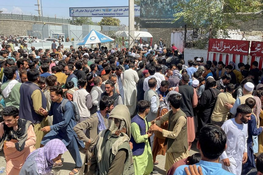 People try to get into Hamid Karzai International Airport in Kabul on Aug 16, 2021.