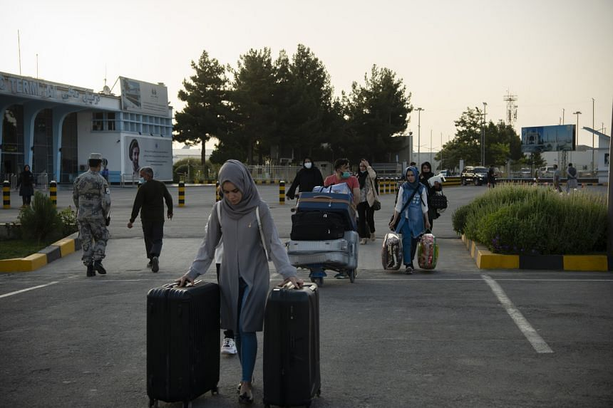 Afghans and travelers pass through checkpoints at the Hamid Karzai International Airport in Kabul ahead of the Taleban's arrival on Aug 15, 2021.