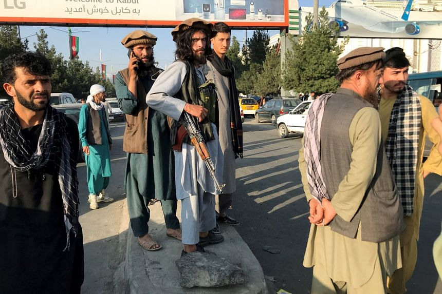 Taleban fighters standing outside Hamid Karzai International Airport in Kabul on Aug 16, 2021.