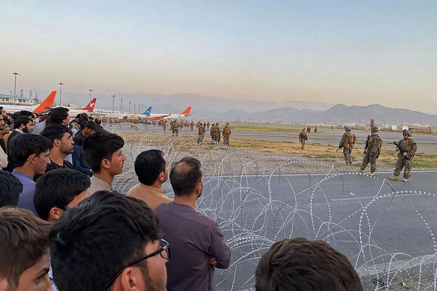 Afghans crowd at the airport as US soldiers stand guard in Kabul on Aug 16, 2021.