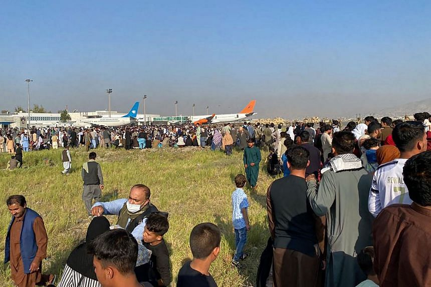 Afghans crowd at the airport as they wait to leave from Kabul, on Aug 16, 2021.