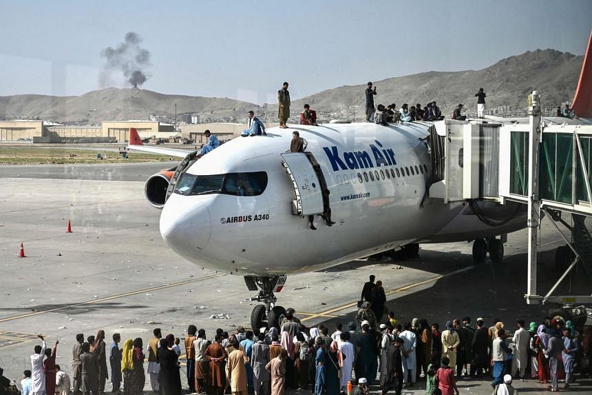 Afghan people climb atop a plane as they wait at the Kabul airport, on Aug 16, 2021.