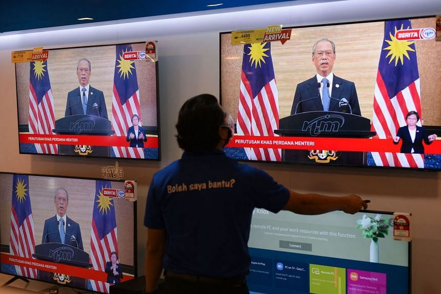 Televisions screens at a mall in Kuala Lumpur are seen showing Malaysian Prime Minister Muhyiddin Yassin during his live address on Aug 16, 2021.