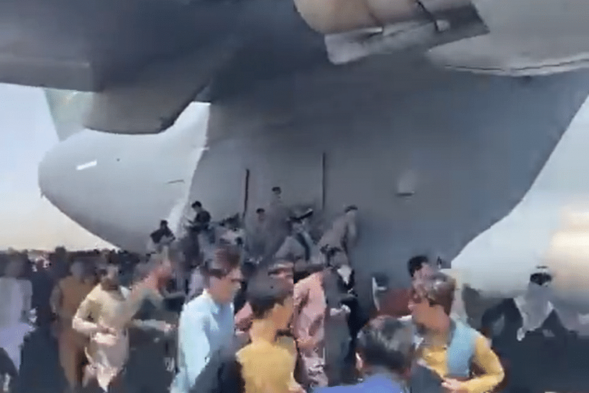 Crowds of people were seen attempting to climb up an US Air Force plane at Kabul airport, on Aug 16, 2021.
