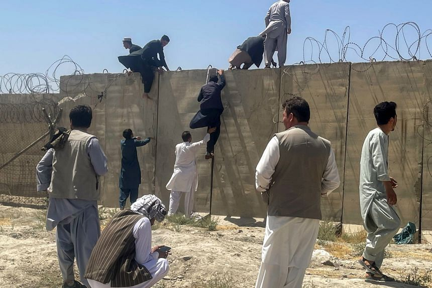 Men try to get inside Hamid Karzai International Airport in Kabul, Afghanistan on Aug 16, 2021.