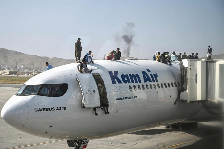 Afghan people climb atop a plane as they wait at Kabul airport on Aug16, 2021.