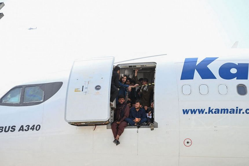 Afghan people climb up on a plane and sit by the door as they wait at Kabul airport, on Aug 16, 2021.