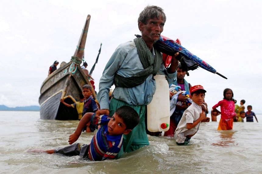 A photo from Sept 10, 2017, showing a Rohingya refugee pulling a child as they walk to the shore in Shah Porir Dwip, Bangladesh.
