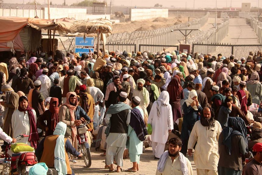 People stranded at the Pakistani-Afghan border wait for its reopening after it was closed by the Taleban, on Aug 11, 2021.
