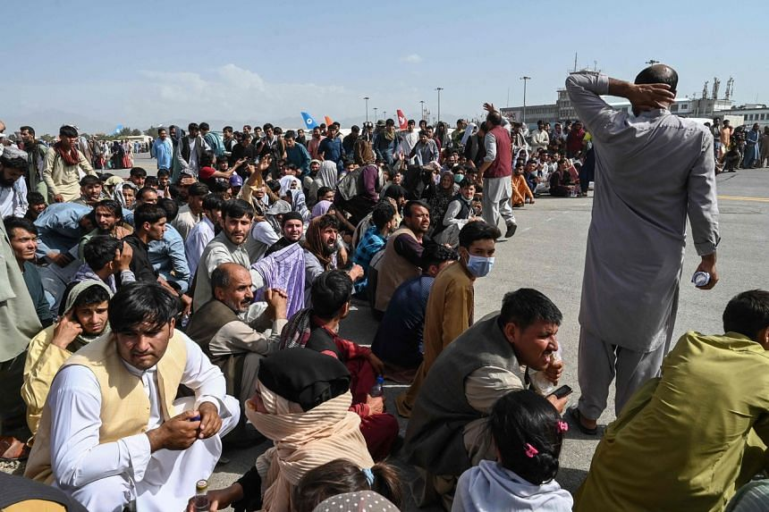 Afghan passengers sit as they wait to leave the Kabul airport on Aug 16, 2021.