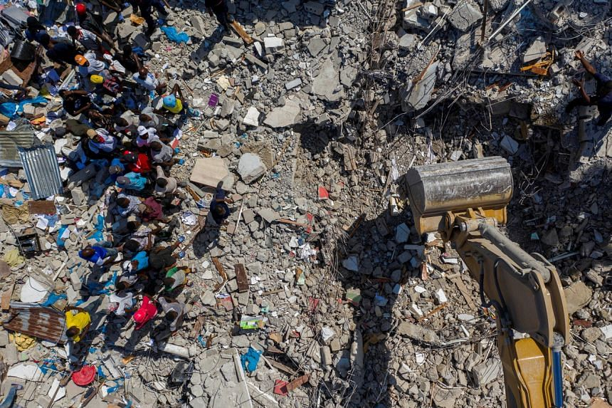 People watch an excavator removing rubble from the site of a collapsed building in Les Cayes, Haiti, on Aug 16, 2021.