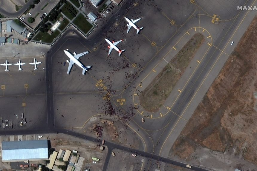 A handout satellite image shows crowds rushing toward parked airplanes on the tarmac of Kabul International Airport, on Aug 16, 2021.