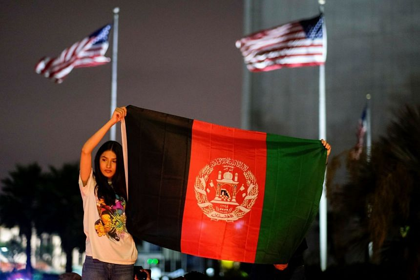 People holding an Afghan flag at a vigil for Afghanistan outside the West LA Federal Building in Los Angeles on Aug 17, 2021.