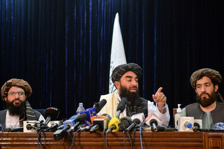 Taleban spokesman Zabihullah Mujahid (centre) gestures as he addresses the group's first press conference on Aug 17 since it took control of Kabul.