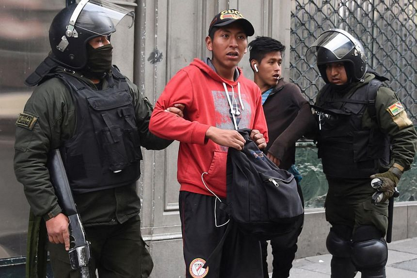A photo from Nov 13, 2019, showing riot police detaining men after clashes erupted between supporters and opponents of leftist Evo Morales' party in La Paz.