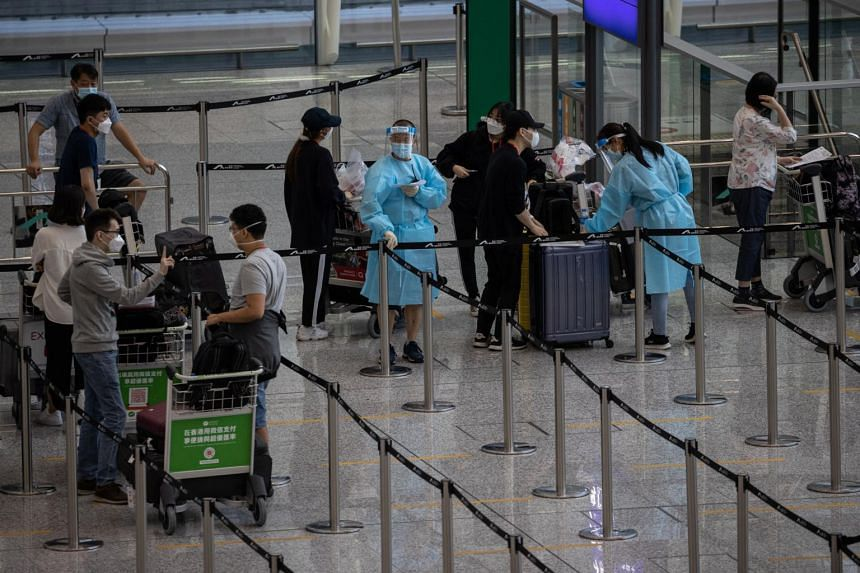 Travellers wait for shuttle buses to mandatory government-designated quarantine hotels at Hong Kong International Airport in Hong Kong, on Aug 17, 2021.