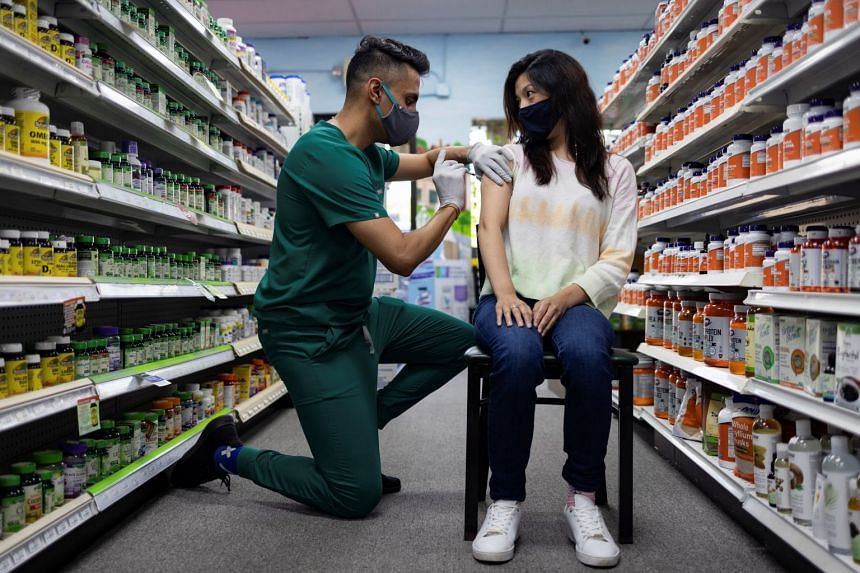 A woman receives the Pfizer-BioNTech vaccine as a booster dose at a pharmacy in the US.