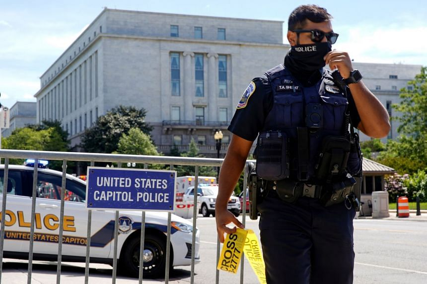 A US Capitol Police officer mans a police barricade as police investigate a bomb threat near the US Capitol in Washington.