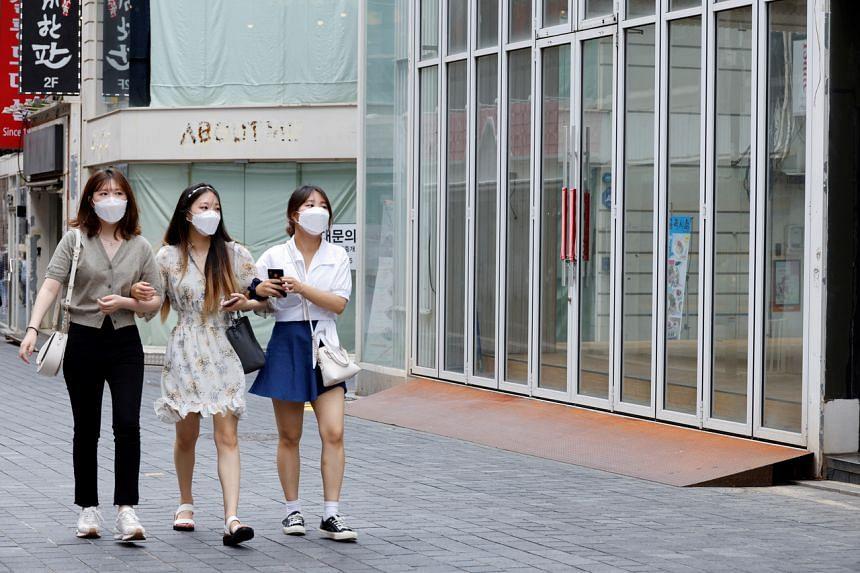 Women wearing masks walk in a shopping district in Seoul,South Korea, on July 9, 2021.