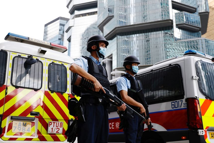 Armed police stand guard as a prison van carrying Andy Li arrives at the high court in Hong Kong on Aug 19.