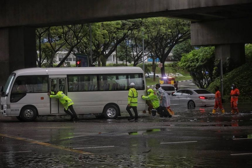 Police pushing a mini-bus off after flood waters receded at the junction of Pasir Ris Drive 12 and Tampines Avenue 10 on Aug 20, 2021.