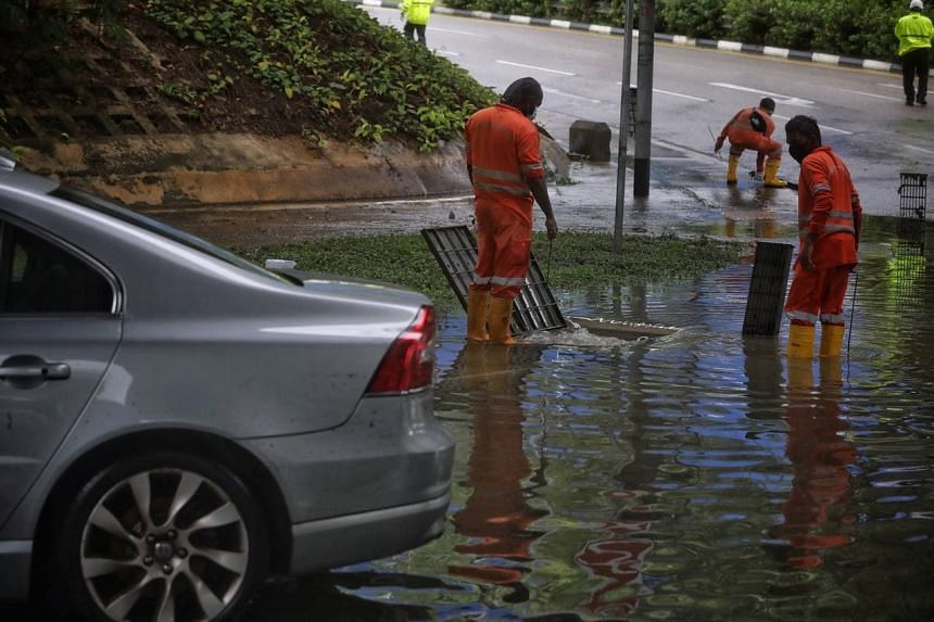 Workers opening drain covers to help flood waters recede at the junction of Pasir Ris Drive 12 and Tampines Avenue 10 on Aug 20, 2021.
