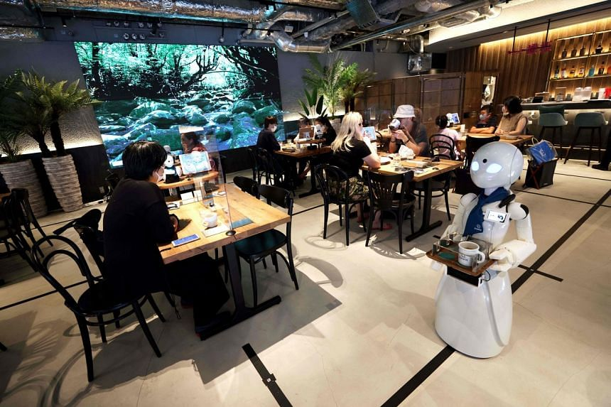A humanoid robot delivers drinks to customers at the Dawn Cafe in Tokyo on Aug 17, 2021.