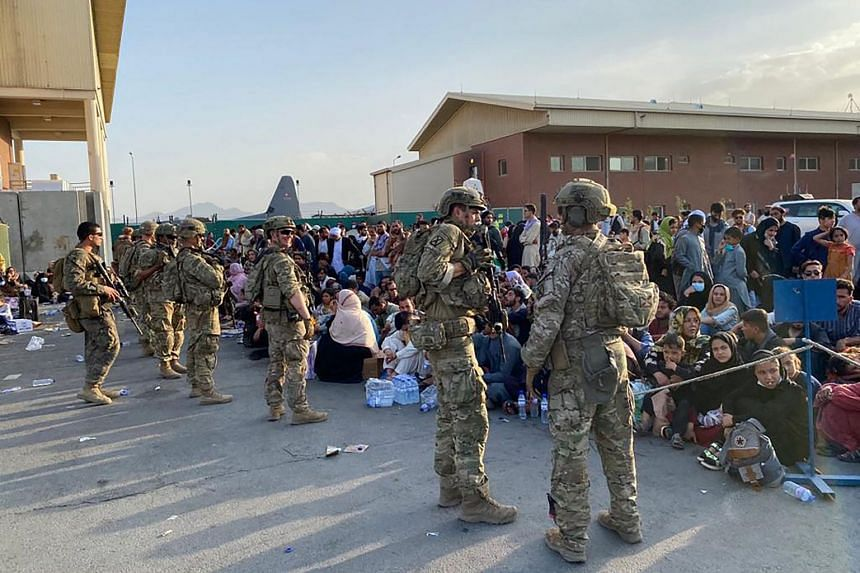 US soldiers stand guard as Afghan people wait to board a US military aircraft to leave Afghanistan, at the military airport in Kabul on Aug 19, 2021.