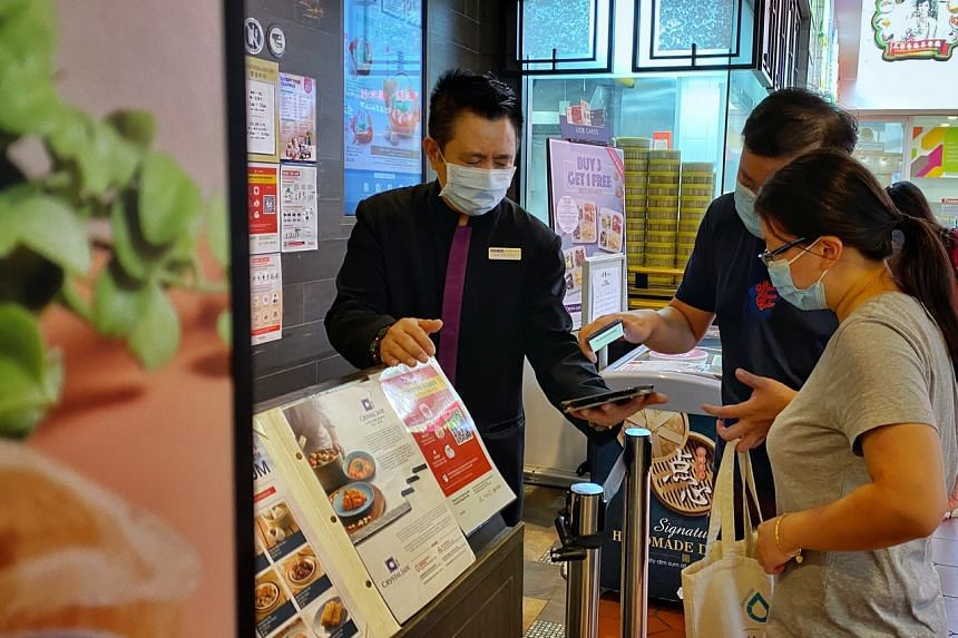 People have their vaccination status checked at a restaurant at Jurong Point on Aug 10, 2021.